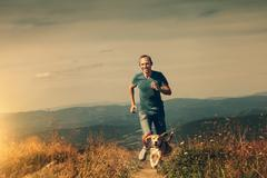 Man running with his dog on the mountain tableland Stock Photos