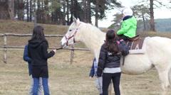 Kid in saddle in horse rehabilitation center for children retarded development Stock Footage
