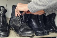 Young man picking a pair of boots from the closet Stock Photos