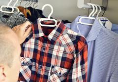 Young man picking a shirt from the closet Stock Photos