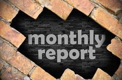 Hole in the brick wall with word monthly report - stock photo