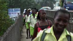 BOY STUDENTS RUN ACROSS BRIDGE OVER DENSU RIVER TOWARDS CAMERA Stock Footage
