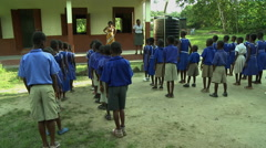 MORNING ASSEMBLY: TEACHER GIVES INSTRUCTIONS TO STUDENTS - stock footage