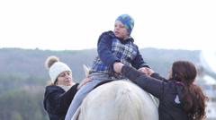 Kid in saddle close contact horse in rehabilitation center for children - stock footage