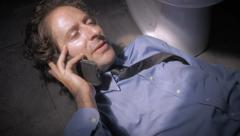 Man in a shirt and tie answers his phone while laying next to a toilet - stock footage