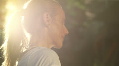 portrait of jogging woman before running  on early mornig with sun flare in back - stock footage