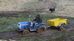 Man farmer drive agrimotor tractor on a wet dirt road - stock footage