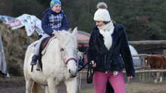 Kid ride a horse in rehabilitation center for children with retarded development Stock Footage