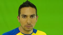Hispanic man in front of green screen applies yellow facial paint Stock Footage