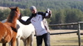 Weekend with horses - man takes selfie by a photo camera for facebook profile Footage