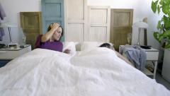 Young woman wakes up feeling hangover and lying with a unknown man Stock Footage