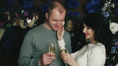 Husband and wife near the Christmas tree drink champagne Stock Footage