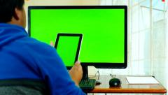 Man from behind sitting and working on computer and tablet with green screen Stock Footage