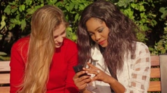 Two girls, caucasian and african, have fun outdoors, watch smartphone, laugh. - stock footage