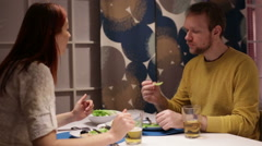 Family eating meal and talking at a table at home - stock footage