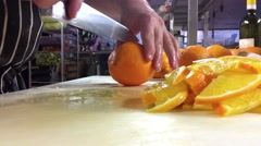 Chef is slicing oranges into half moon slices, at a restaurant kitchen Stock Footage