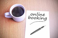 Coffee on the table with note writing writing online booking Stock Photos