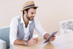 Smiling man holding tablet and disposable cup Stock Photos