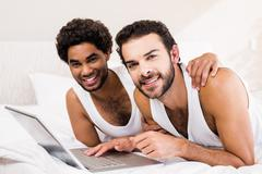 Happy gay couple laying on bed using laptop Kuvituskuvat