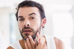 Concentrated man cutting his beard with scissors Stock Photos