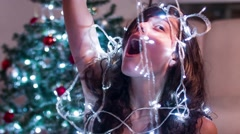 A girl plays with Christmas lights and gives lots of laughs Stock Footage