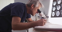 Stock Video Footage of Middle aged male radiologist looking through microscope