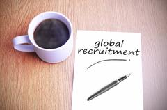 Coffee on the table with note writing global recruitment Stock Photos