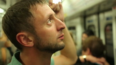 Tired male passenger reading advertisements inside subway train during rush hour Stock Footage