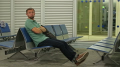 Stock Video Footage of Unhappy male passenger sitting at waiting room, flight canceled or delayed