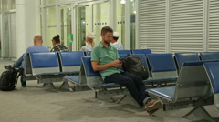 Happy guy checking time on smartphone clock, man walking for flight registration - stock footage