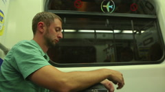 Young man reading news online, using app, texting on smartphone in metro train Stock Footage