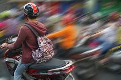Motorbikes compete in heavy traffic - stock photo