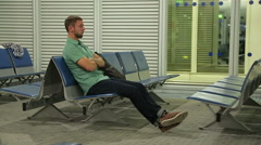 Stock Video Footage of Annoyed male passenger waiting for transfer at airport, using phone application