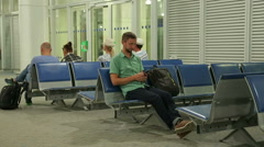 Happy guy checking time on smartphone clock, man walking for flight registration Stock Footage