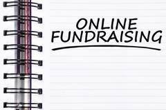 Online fundraising words on spring note book Stock Photos
