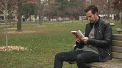 Male Reading Book while Sitting on Park Bench. Wide Shot. Stock Footage