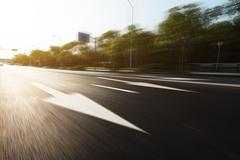 Sunlight and empty asphalt road with traffic sign Stock Photos