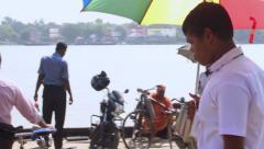 A young man gets onto a traditional Inidan passenger boat Stock Footage