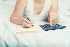 young woman on the bed with a notebook and calculator Credit, mortgage. - stock photo
