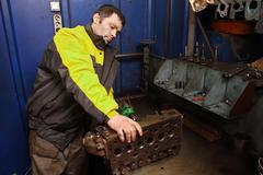 Young car mechanic cleans channels of the cylinder head engine. Stock Photos