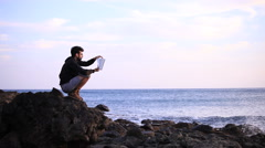 Guy reading a book crouched on the rock Stock Footage