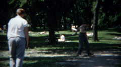 1954: Men practicing softball on a hot lazy day on the lakefront beach. Stock Footage