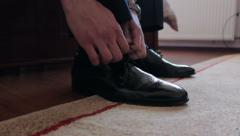 Man is tying his black shoes Stock Footage
