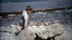 1954: Boy exploring a water seawall holding back the crashing waves. Stock Footage