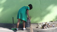 Girl scout sweeping the street with broom Stock Footage