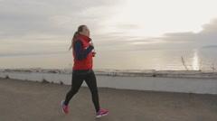 Runner woman running seaside. athlete fitness silhouette sunrise jogging workout Stock Footage