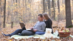 Couple with laptop in the autumn forest Stock Footage