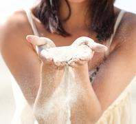 Female hands holding sand - stock photo