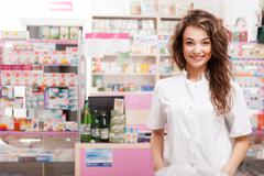 Smiling doctor in front of pharmacy desk - stock photo