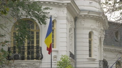 Romanian flag waving in front of a building in Bucharest Stock Footage
